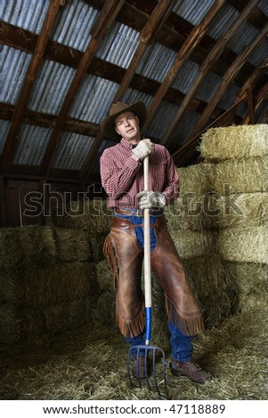 Man wearing a cowboy hat and chaps leaning on a pitchfork. Behind him are bales of hay. Vertical shot.