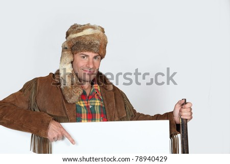 Man wearing a fur hat pointing to a blank poster
