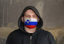 Man Wearing a hood and a Slovenia flag Mask to Protect him virus.