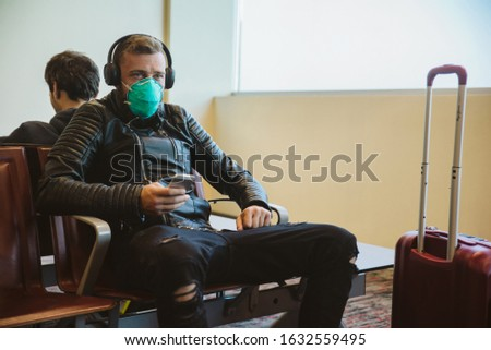 Man wearing a mask protection at an airport. Epidemic corona virus infection, flu sickness and travel illness concept