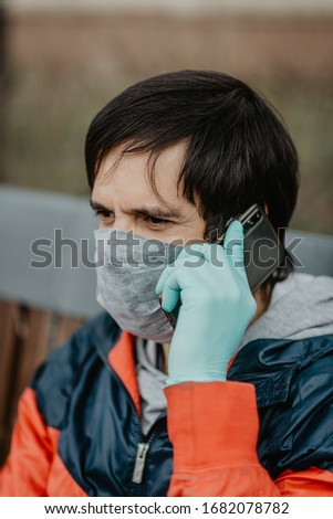 Man wearing a medical face mask and gloves talking on smartphone