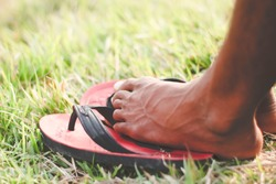 Man wearing a pair of colorful sandal against a blurry background. Alone boy sitting on the grass land. Feeling sad depressed or daydreaming. Copyspace. Strong leg with vein visible. Bodypart.Z