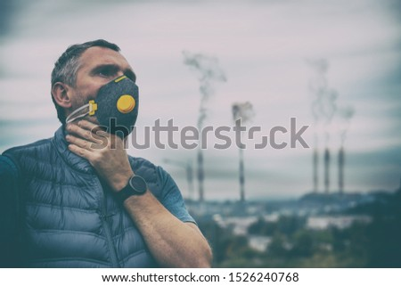 Man wearing a real anti-pollution, anti-smog and viruses face mask; dense smog in air.