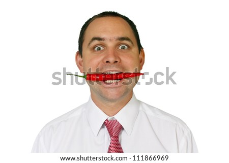 Man wearing a shirt and tie who has a red chili between his teeth and a slightly crazy expression in his eyes