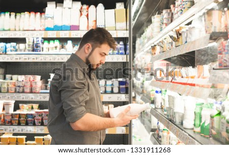Man wearing a shirt is standing in a supermarket in the milk department and looking at a bottle of milk holds in his hand. Buyer reads the milk label, checks the expiration date.