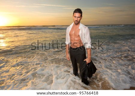 man wearing a suit all wet on the sea at the beach