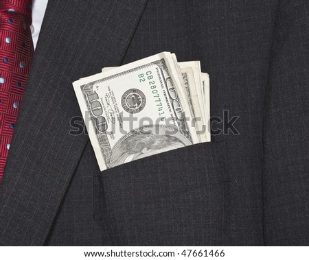 man wearing a suit and red tie, with pocket full of american dollars - stock photo