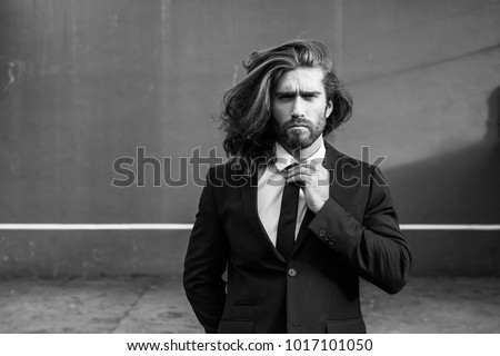 Man wearing a suit in a tennis court