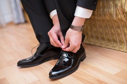 Man wearing a suit putting his brown shoes on. Hands and shoe close-up. Closeup view of male hands lacing beautiful elegant shoes. wedding day. groom tie his shoe
