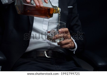 Man wearing a suit whiskey glass of liquor