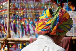 Man wearing a turban in a market place in India.