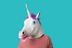 man wearing a unicorn mask and a red and white striped t-shirt on a blue background with some blank space around him