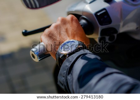 Man wearing a watch. Man is on a motorcycle, ready to go.
