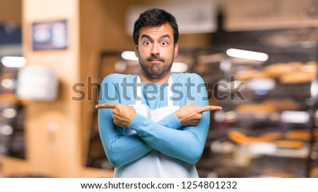 Man wearing an apron pointing to the laterals having doubts. Undecided person in a bakery