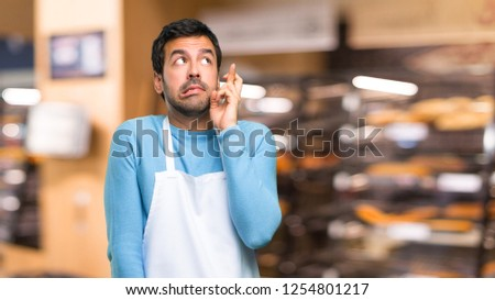 Man wearing an apron with fingers crossing and wishing the best. Making a wish. in a bakery #1254801217