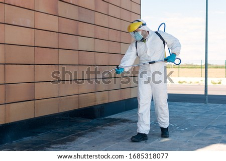 Man wearing an NBC personal protective equipment (ppe) suit, gloves, mask, and face shield, cleaning the streets with a backpack of pressurized spray disinfectant water to remove covid-19 coronavirus.