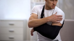 Man wearing arm sling feeling pain in shoulder, result of trauma, orthopedics