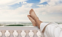 man wearing bathrobe resting feet on Italian balustrades with ocean waves in the background