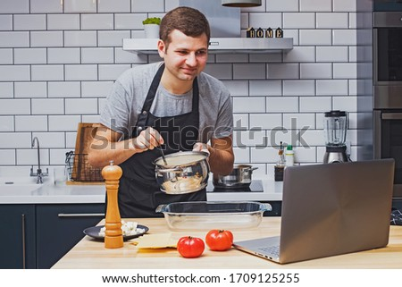 Man wearing black apron in the modern kitchen looking for recipes on his laptop. Cooking in home, online recipe, remote cooking classes