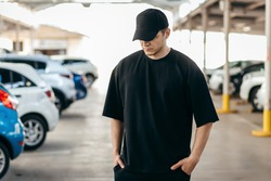 Man wearing black blank t-shirt and a black baseball cap with space for your logo or design. Mock up