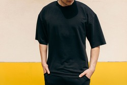 Man wearing black blank t-shirt with space for your logo or design. Mock up