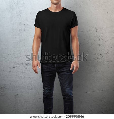 Man wearing black t-shirt. Concrete wall background