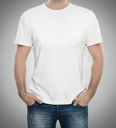 Man wearing blank t-shirt isolated on gray background with copy space