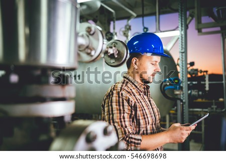 Man wearing blue hardhat using tablet at Natural gas processing facility - Shutterstock ID 546698698