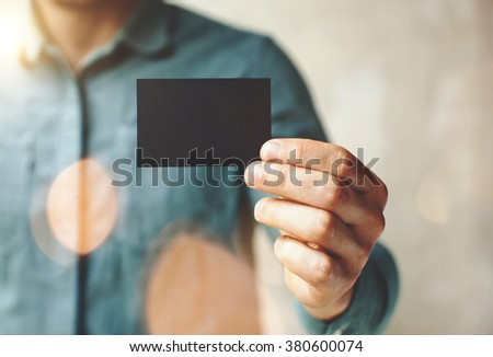 Man wearing blue jeans shirt and showing blank black business card. Blurred background. Horizontal mockup #380600074