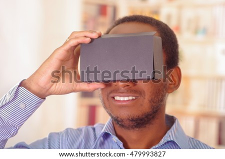 Man wearing blue shirt testing vitrual reality mobile device, holding glasses in front of eyes and smiling #479993827
