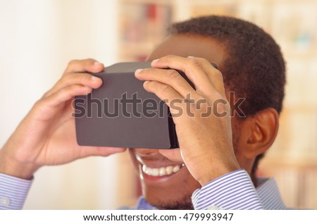 Man wearing blue shirt testing vitrual reality mobile device, holding glasses in front of eyes and smiling #479993947