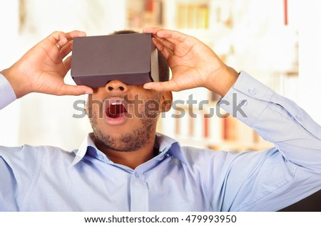 Man wearing blue shirt testing vitrual reality mobile device, holding glasses in front of eyes and smiling #479993950