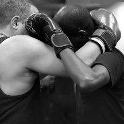 Man wearing boxing  gloves has second man with gloves in a close up head clutch in a martial arts training bout.