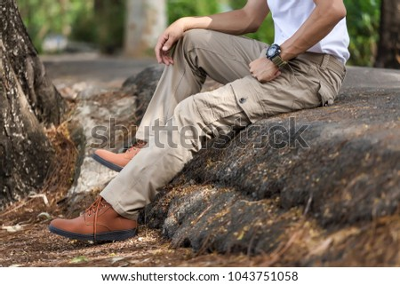 Man wearing brown cargo pants and sitting in the nature park #1043751058