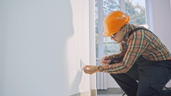 Man wearing brown shirt and dungarees working on electrical wall socket wires using screwdriver, electrician concept.