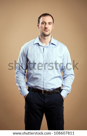 Man wearing business outfit standing relaxed.