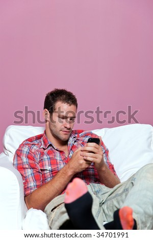 Man wearing casual clothing sat in an armchair text messaging on his mobile phone. - stock photo