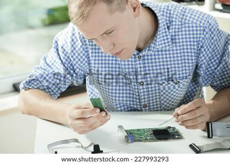 Man wearing check shirt repairing his computer