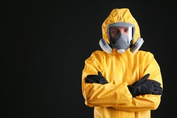 Man wearing chemical protective suit on black background, space for text. Virus research