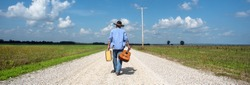 Man wearing cowboy hat walking down one lane country road alone with old suitcase and acoustic guitar, blue sky, white clouds, independent, traveling, music, rural country, back to camera, portrait