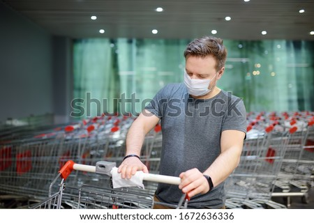 Man wearing disposable medical face mask wipes the shopping cart handle with a disinfecting cloth in supermarket. Safety during coronavirus outbreak. Epidemic of virus covid.