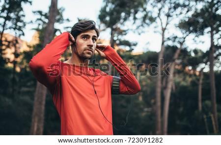 Man wearing earphones looking away. Runner listening to music during morning jog.
