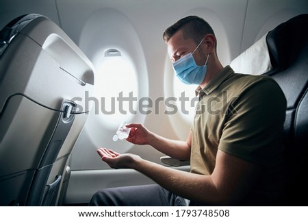 Man wearing face mask and using hand sanitizer inside airplane during flight. Themes new normal, coronavirus and personal protection.