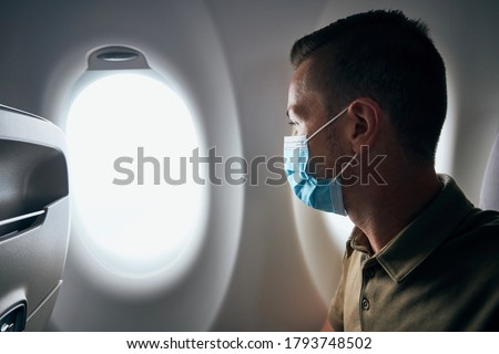Man wearing face mask inside airplane during flight. Themes new normal, coronavirus and personal protection.  Foto stock ©