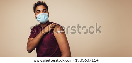 Man wearing face mask showing his vaccinated arm. Man in protective face mask received a corona vaccine looking away on brown background.
