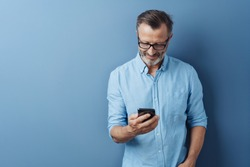Man wearing glasses standing smiling as he reads a text message on his mobile phone against a blue studio background with copy space