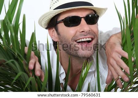 Man wearing hat behind bush