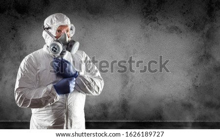 Man Wearing Hazmat Suit, Protective Gas Mask and Goggles Against Dark Wall.