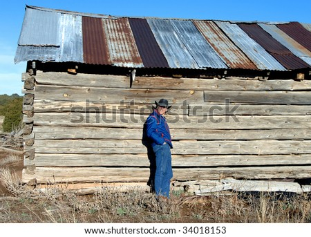 Man wearing jeans and a cowboy hat, leans against the wood and adobe wall of an abandoned cabin.  Building is outside of Alberquerque, New Mexico.