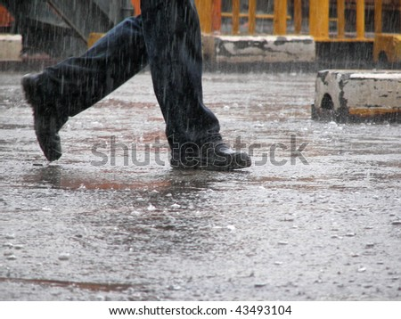 Man wearing jeans and working shoes walking under the heavy rain